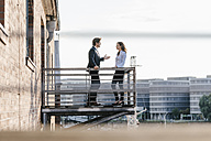 Business people standing on balcony, discussing - KNSF02809