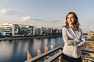 Businesswoman standing on terrace of industrial building - KNSF02818