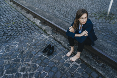 Barefoot businesswoman sitting on rail - KNSF02821