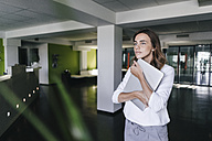 Businesswoman standing in office, holding laptop - KNSF02824