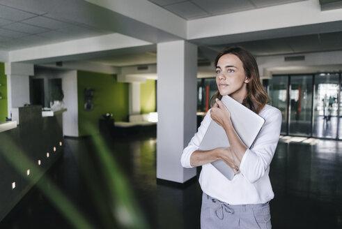 Businesswoman standing in office, holding laptop - KNSF02824