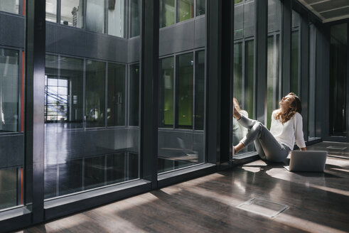 Businesswoman with laptop, sitting on floor, daydreaming - KNSF02827