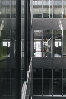 Woman standing at office window, looking up - KNSF02833