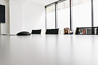 Exhausted businesswoman in conference room - KNSF02848