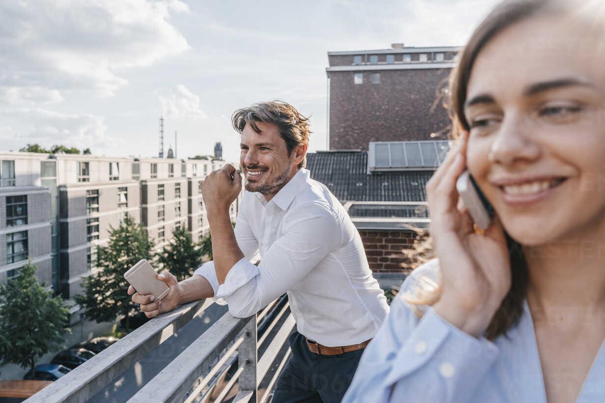 Business people standing on balcony, using smartphone - KNSF02863 - Kniel Synnatzschke/Westend61
