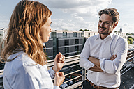 Business people standing on balcony, discussing - KNSF02866
