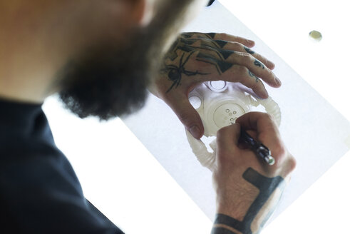 Tattoo artist designing motif on light table in studio - IGGF00161