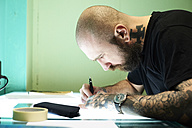 Tattoo artist designing motif on light table in studio - IGGF00164