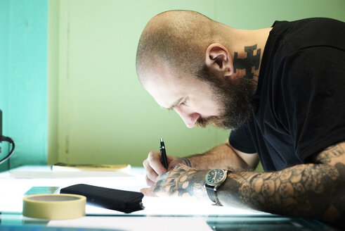 Tattoo artist designing motif on light table in studio - IGGF00164