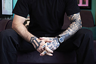 Arms of tattoo artist in studio - IGGF00170