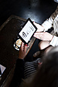 Two businesswomen with tablet having a meeting at a coffee shop - IGGF00173
