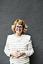 Portrait of smiling senior businesswoman against grey wall - IGGF00182
