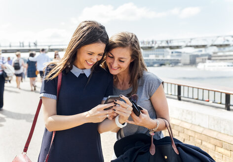 UK, London, two women sharing smartphone at banks of the Thames River - MGOF03600