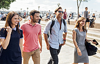 UK, London, group of friends walking along the banks of the Thames River - MGOF03603