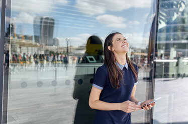 UK, London, happy woman with smartphone in the city - MGOF03612