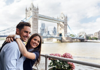 UK, London, smiling couple with the Tower Bridge in the background - MGOF03624