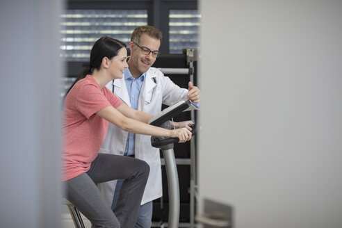 Smiling doctor and patient on exercise machine - ZEF14554
