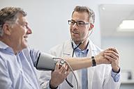 Doctor taking blood pressure of senior patient in medical practice - ZEF14563