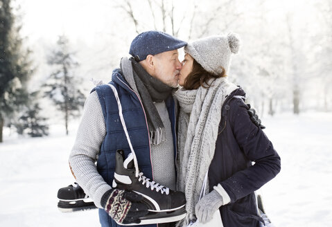 Senior couple with ice skates kissing in winter landscape - HAPF02128
