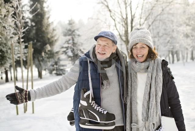 Happy senior couple with ice skates in winter landscape - HAPF02131