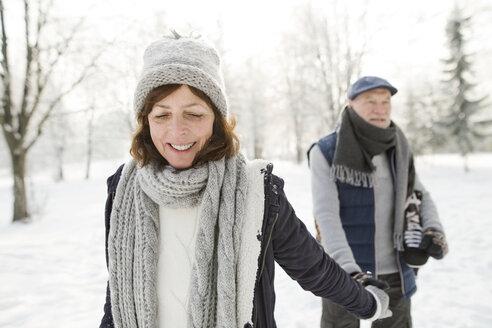 Happy senior couple with ice skates walking in winter landscape - HAPF02134