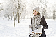 Smiling senior woman with ice skates in winter forest - HAPF02143