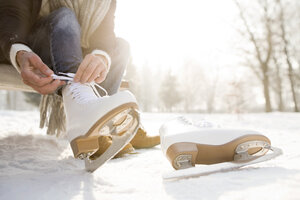 Woman sitting on bench in winter landscape putting on ice skates - HAPF02146