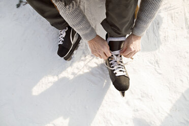 Man putting on ice skates - HAPF02149