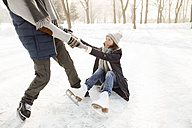 Man helping ice skating woman getting up from frozen lake - HAPF02161