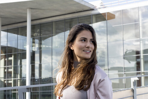 Young woman smiling in front of office building - LMF00776