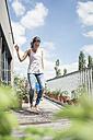 Happy woman jumping on balcony - JOSF01552