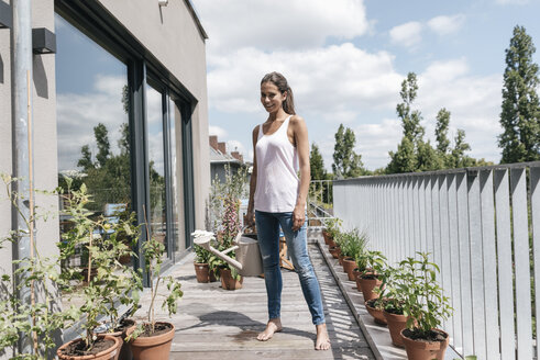 Smiling woman on balcony holding watering can - JOSF01561