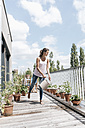 Smiling woman on balcony watering plants - JOSF01564