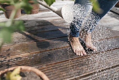 Woman with watering can pouring water over her feet - JOSF01567