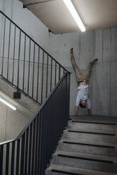 Young man doing a handstand in staircase - JOSF01570
