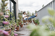Smiling woman relaxing on balcony using tablet - JOSF01573