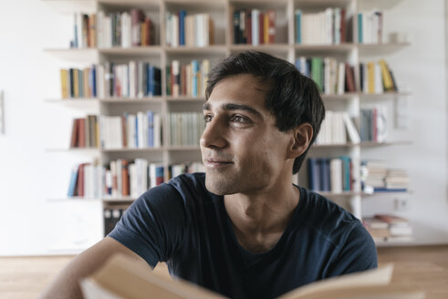 Smiling young man with book at home looking sideways - JOSF01585