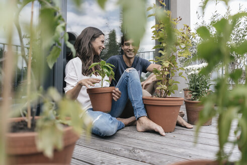 Happy couple with plants relaxing on balcony - JOSF01591