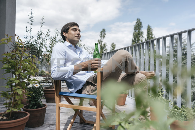 Man with bottle relaxing on balcony - JOSF01594