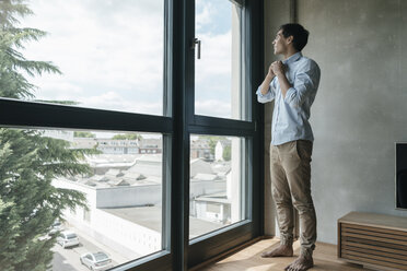 Young man buttoning his shirt looking out of window - JOSF01597