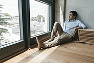 Man sitting on the floor looking out of window - JOSF01600