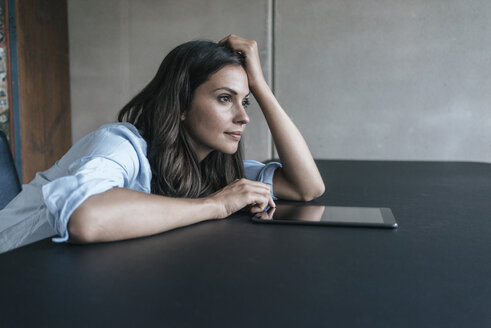 Woman with tablet leaning on table - JOSF01612