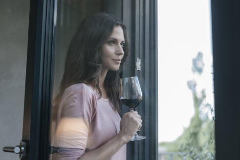 Smiling woman holding glass of red wine looking out of window - JOSF01615