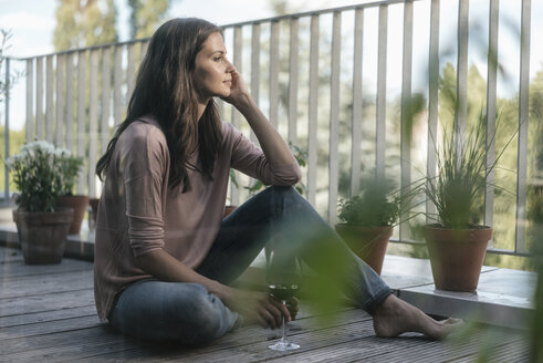 Woman with glass of red wine relaxing on balcony - JOSF01618