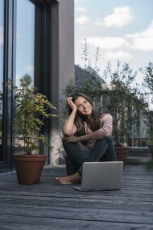 Smiling woman with laptop sitting on balcony - JOSF01621