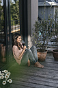 Woman with glass of red wine relaxing on balcony - JOSF01624