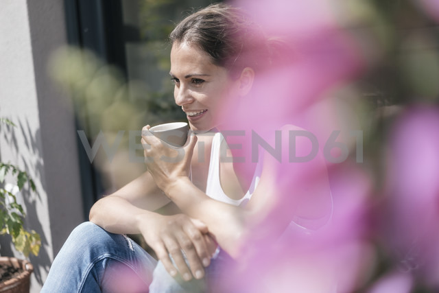 Smiling woman relaxing on balcony - JOSF01627