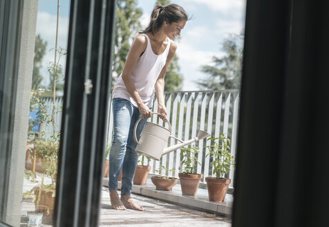 Smiling woman on balcony watering plants - JOSF01630