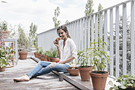 Smiling woman eating croissant with jam on balcony - JOSF01633