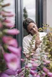 Woman caring for plant on balcony - JOSF01636